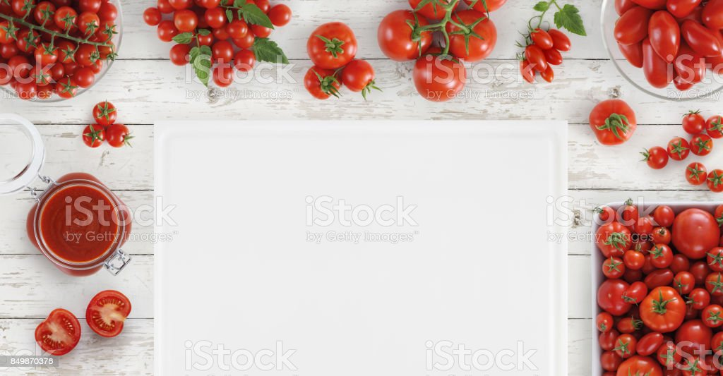 food above with many fresh tomatoes, sauce and blank cutting boards on kitchen white work top, copy space, top view stock photo