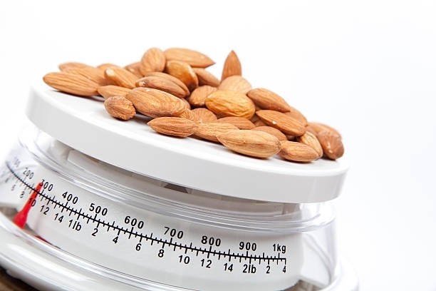food almonds on scale - portion bildbanksfoton och bilder