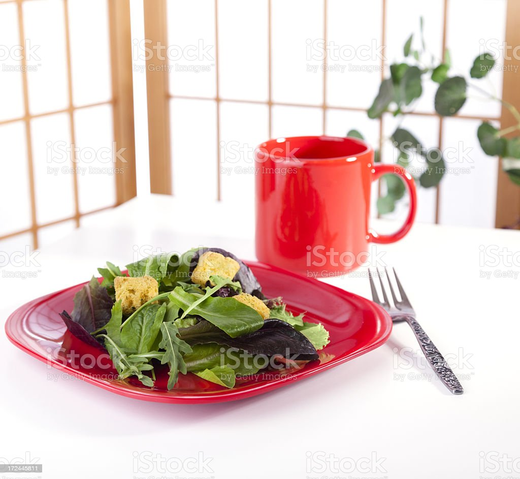 Food and Drink:  Green salad with cup on red dishware stock photo