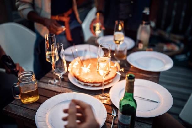 Food and drink on table with sparklers at rooftop party stock photo
