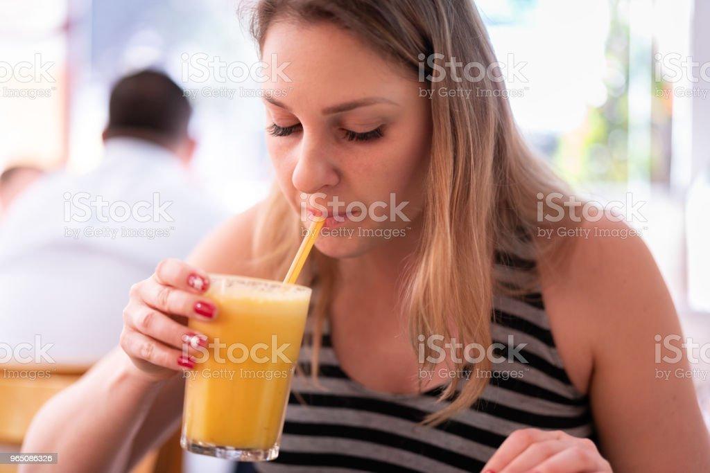 Woman drinking orange juice royalty-free stock photo