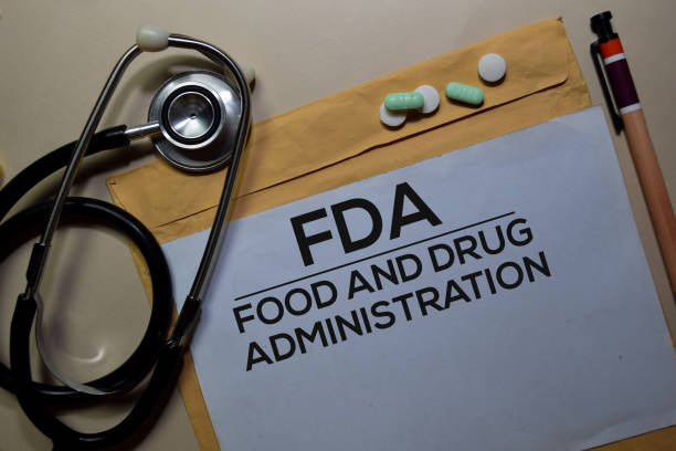 FDA - Food and Drug Administration text on document above brown envelope and stethoscope. Healthcare or medical concept stock photo