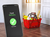 istock Food and eats delivery concept. Mobile phone and shopping basket with grocery in front of open door. 1200326248