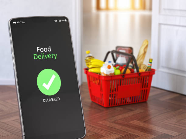 Food and eats delivery concept. Mobile phone and shopping basket with grocery in front of open door. stock photo