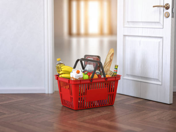 Food and eats delivery concept. Shopping basket with grocery in front of open door. stock photo