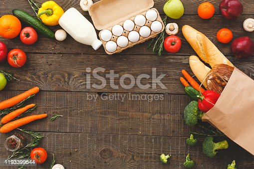 Flat lay view of raw organic vegetables with fresh ingredients for healthy cooking, eggs, bottle with milk and bread in paper bag on wooden table with copy space
