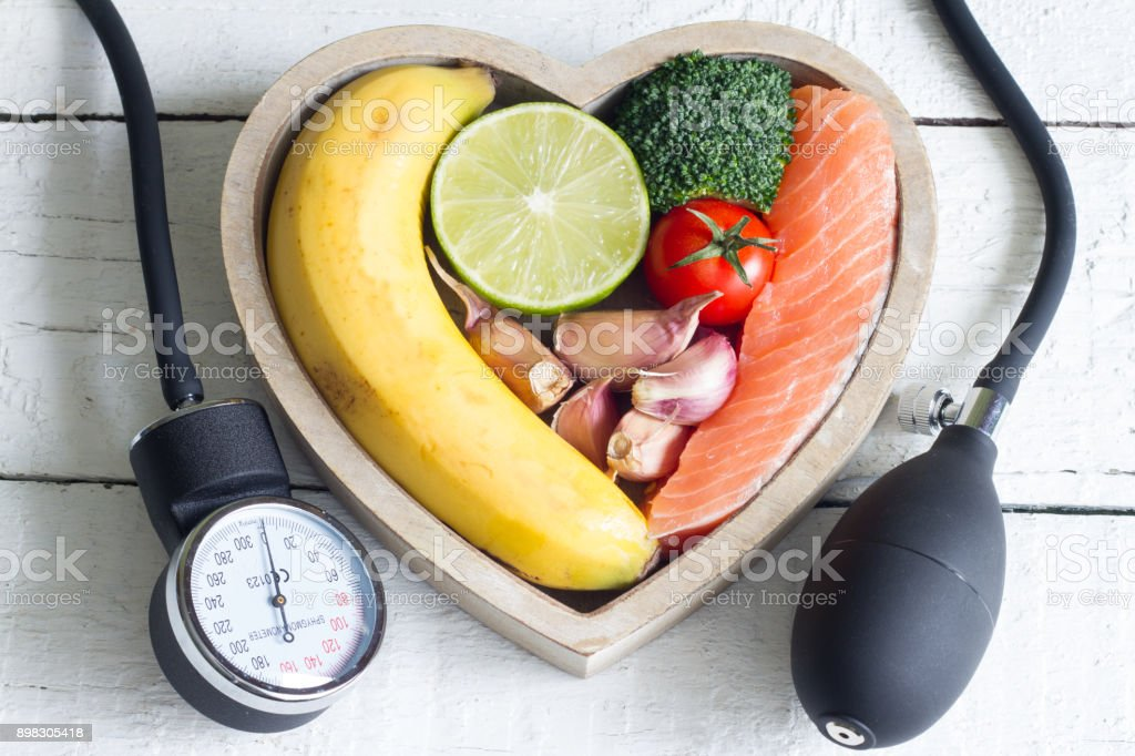 Food and healthy heart diet concept with blood preasure guage on white planks stock photo