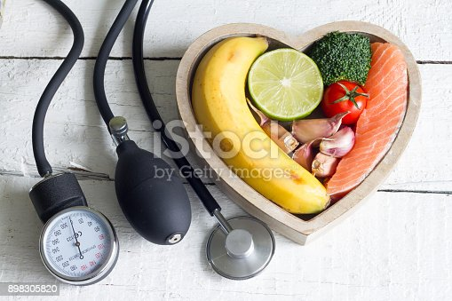 istock Food and healthy heart diet concept with blood preasure guage on white planks 898305820