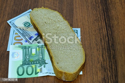 On the table are bills and a piece of bread, the photograph tells that the name money can buy food.