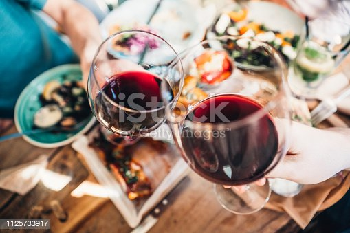 Close up of a friends toasting with red wine at restaurant