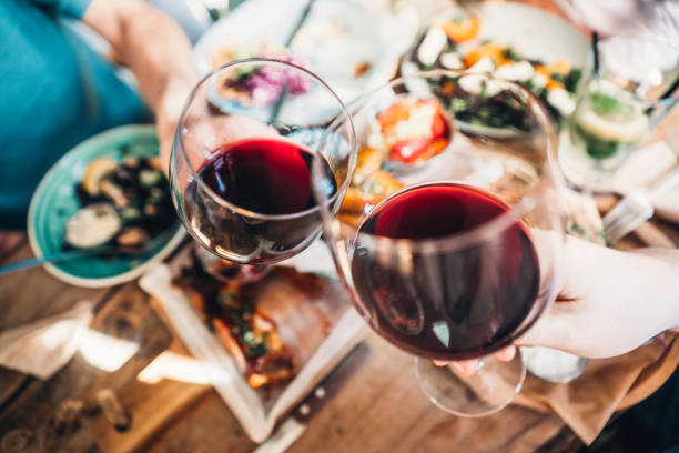 Food and wine brings people together Close up of a friends toasting with red wine at restaurant wine stock pictures, royalty-free photos & images