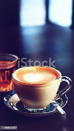 Hot coffee with beautiful latte art on wooden coffee table, vintage color tone process and selective focus for business food and drink background