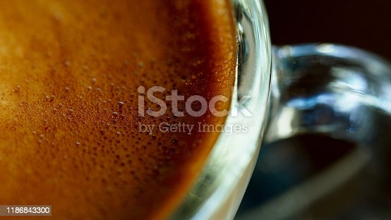 Closeup bubble foam of hot coffee with beautiful latte art on wooden coffee table, vintage color tone process and selective focus for business food and drink background