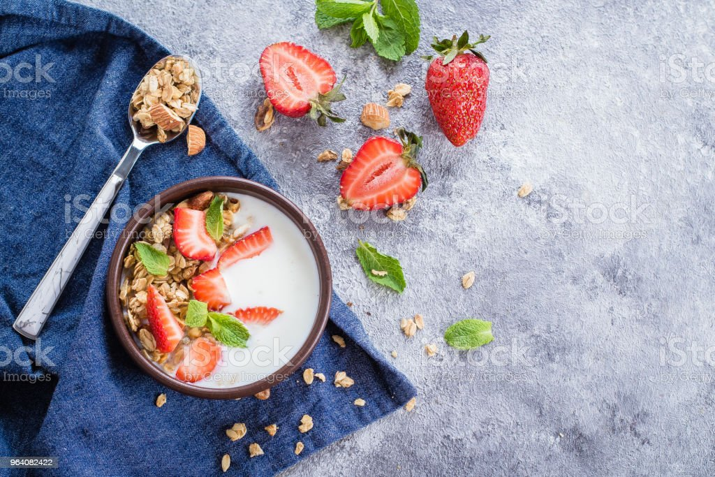 Food Background. Breakfast with yogurt, granola of muesli and strawberries on gray concrete table background. Healthy Diet Food Concept. Top view, copy space, flat lay - Royalty-free Antioxidant Stock Photo