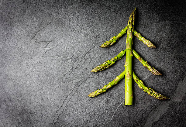 food background. christmas tree made from asparagus healthy holiday concept - veganes weihnachtsessen stock-fotos und bilder