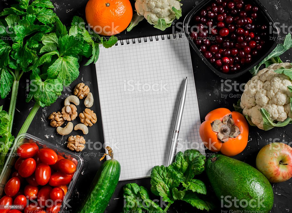 Food background. Fresh vegetables, fruits, blank notepad on a dark background. stock photo
