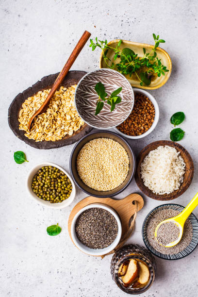 food background - rice, chia seeds, nuts, oatmeal, buckwheat, quinoa, mung beans and greens on a white background. - dieta macrobiotica foto e immagini stock