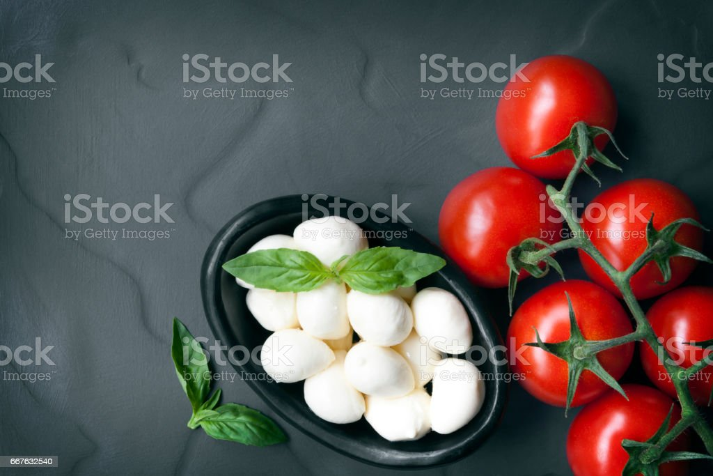 Food Background Slate with Baby Mozzarella Balls Vine Tomatoes and Basil stock photo