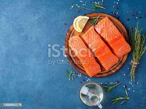 Food background, sliced portions large salmon fillet steaks on chopping board on dark blue concrete table, copy space, top view.
