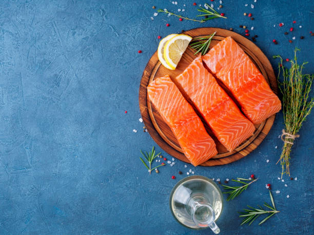 food background, sliced portions large salmon fillet steaks on chopping board on dark blue concrete table, copy space, top view - salmon seafood stock photos and pictures