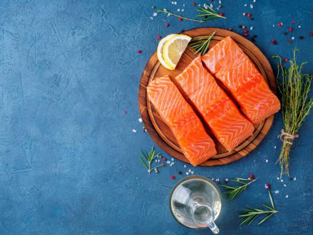 fondo de alimentos, en rodajas bistecs de filete de salmón grande porciones en la tajadera en oscurezca tabla cemento azul, espacio de copia, vista superior - comida cruda fotografías e imágenes de stock
