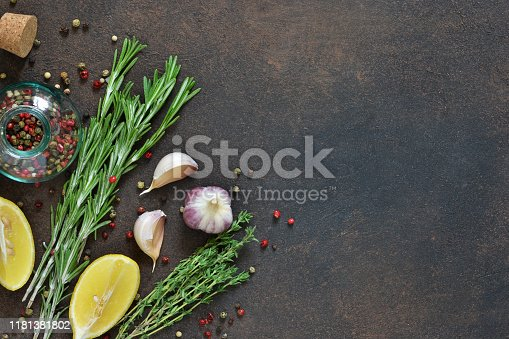 istock Food background - spices.A set of spices: chili, paprika, garlic, salt, lemon, rosemary, thyme and olive oil on a concrete background. 1181381802