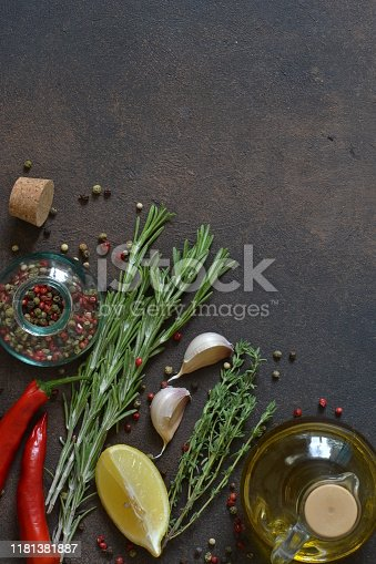 istock Food background - spices.A set of spices: chili, paprika, garlic, salt, lemon, rosemary, thyme and olive oil on a concrete background. 1181381887