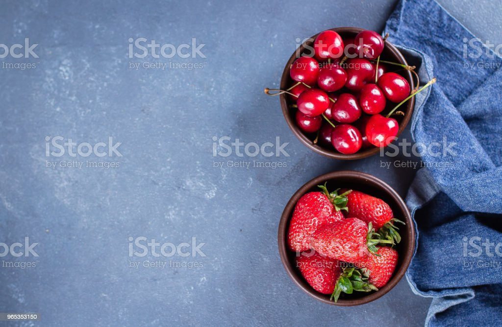 Food Background. Summer Berries Strawberry and Cherry in wooden plate on blue concrete table background. Healthy Concept. Top view, copy space royalty-free stock photo