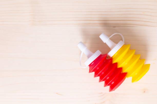 fundo de alimentos ketchup de tomate e mostarda squeeze garrafas em fundo de madeira - squeeze bottle - fotografias e filmes do acervo
