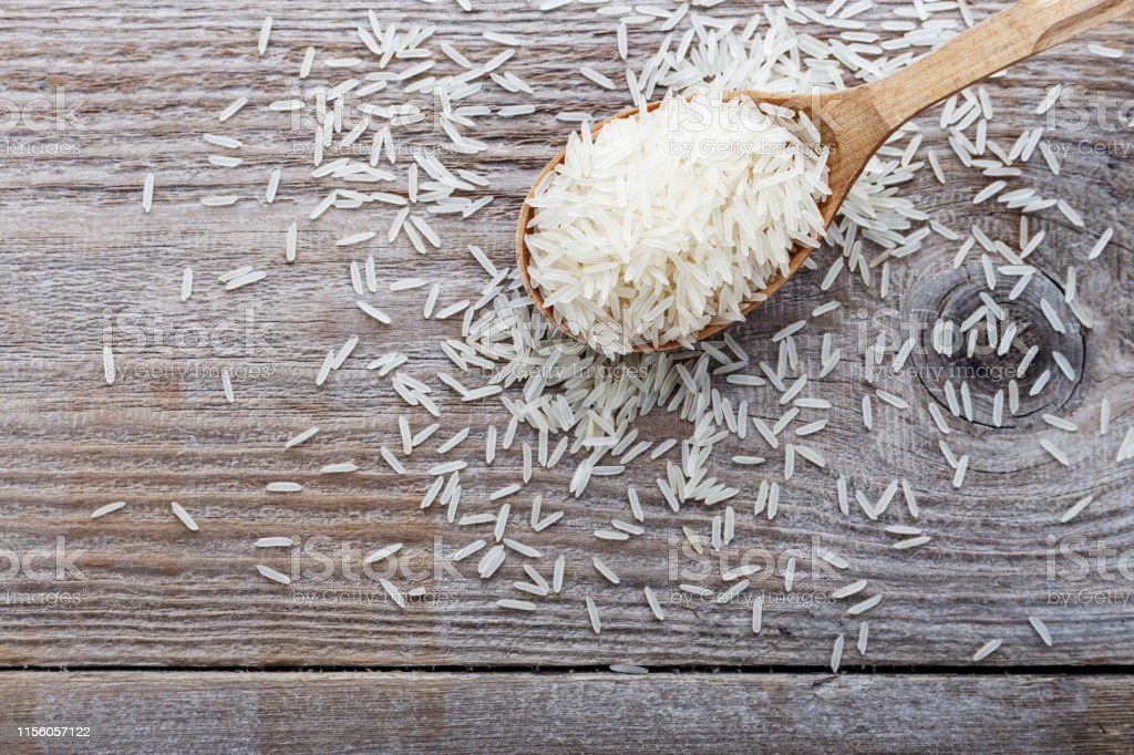 food background. white rice in a wooden spoon. top view