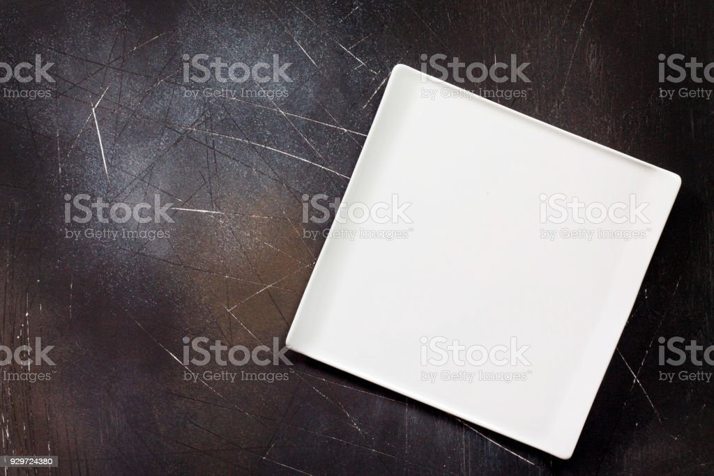 Food background. White square plate on a dark slate table. Copy...