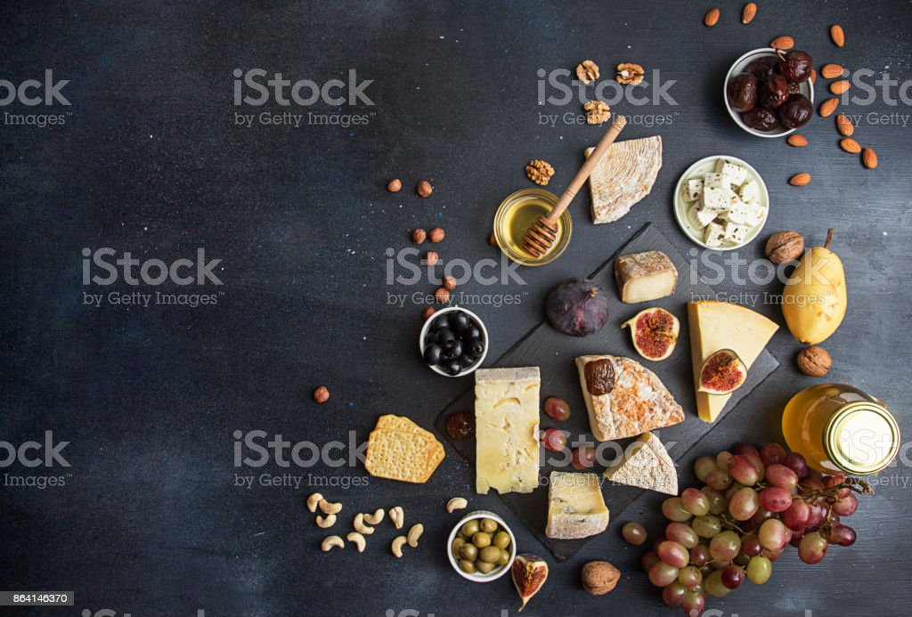 Food background with cheese. Blocks of moldy cheese, grapes, figs, honey, pear, dates, pickled prunes, nuts over on dark background. Copy space. Top view royalty-free stock photo