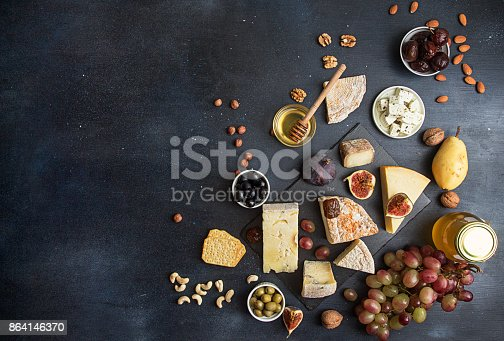 istock Food background with cheese. Blocks of moldy cheese, grapes, figs, honey, pear, dates, pickled prunes, nuts over on dark background. Copy space. Top view 864146370