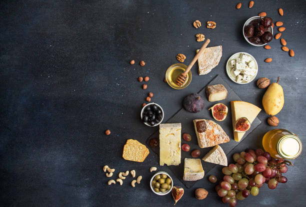 food background with cheese. blocks of moldy cheese, grapes, figs, honey, pear, dates, pickled prunes, nuts over on dark background. copy space. top view - food styling stock photos and pictures