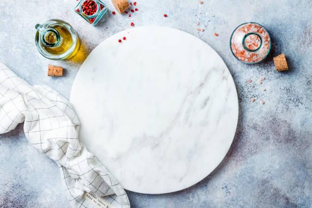 Essenhintergrund mit freiem Platz für Text. Olivenöl, Gewürze um weißes Marmorbrett auf hellgrauem Steintisch. Gesundes Kochkonzept mit Kopierraum. Ansicht von oben. – Foto