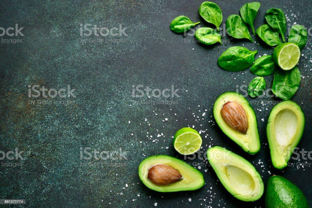 Essen-Hintergrund mit grünem Gemüse: Avocado, Babyspinat und Kalk – Foto