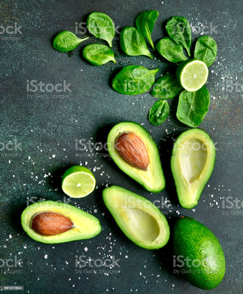 Food background with green vegetables : avocado,baby spinach and lime stock photo