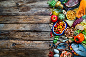 Food and drink backgrounds: top view of a wooden with a large variety of food placed at the right border leaving useful copy space for text and/or logo. The composition includes raw meat, raw fish, cereals, shrimps, fruits, vegetables, eggs, legumes, spices, pasta, nuts, crackers among others. High resolution 42Mp studio digital capture taken with SONY A7rII and Zeiss Batis 40mm F2.0 CF lens