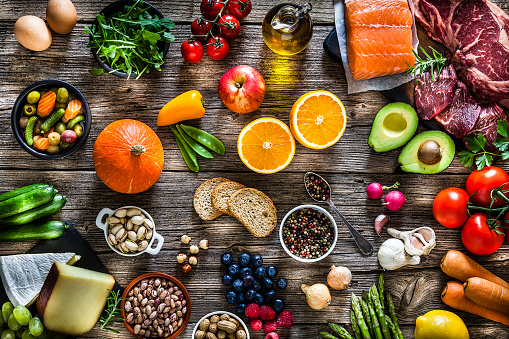 Food backgrounds: top view of a rustic wooden table filled with different types of food. The composition includes raw beef steak, raw salmon fillet, fruits, vegetables, cheese, bread, eggs, legumes, olive oil and nuts. DSRL studio photo taken with Canon EOS 5D Mk II and Canon EF 70-200mm f/2.8L IS II USM Telephoto Zoom Lens
