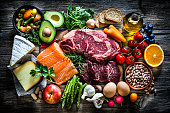 Food backgrounds: top view of a rustic wooden table filled with different types of food. At the center of the frame is a cutting board with beef steak and a salmon fillet and all around it is a large variety of food like fruits, vegetables, cheese, bread, eggs, legumes, olive oil and nuts. Low key DSRL studio photo taken with Canon EOS 5D Mk II and Canon EF 70-200mm f/2.8L IS II USM Telephoto Zoom Lens