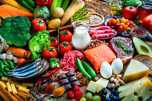Food and drink backgrounds: top view of a wooden table filled with a large variety of food. The composition includes minced meat, sausages, raw fish, shrimps, cereals, fruits, vegetables, dairy products, a red wine bottle, legumes, spices, pasta, olive oil, nuts, honey, among others. High resolution 42Mp studio digital capture taken with SONY A7rII and Zeiss Batis 40mm F2.0 CF lens