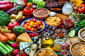 Food and drink backgrounds: high angle view of a wooden table filled with a large variety of food. The composition includes fruits, vegetables, cooking oil, cereal,  dairy products, legumes, spices, herbs, pasta, bread, nuts, cheese, eggs, milk, preserves, chocolate, roasted coffee beans among others. High resolution 42Mp studio digital capture taken with SONY A7rII and Zeiss Batis 40mm F2.0 CF lens