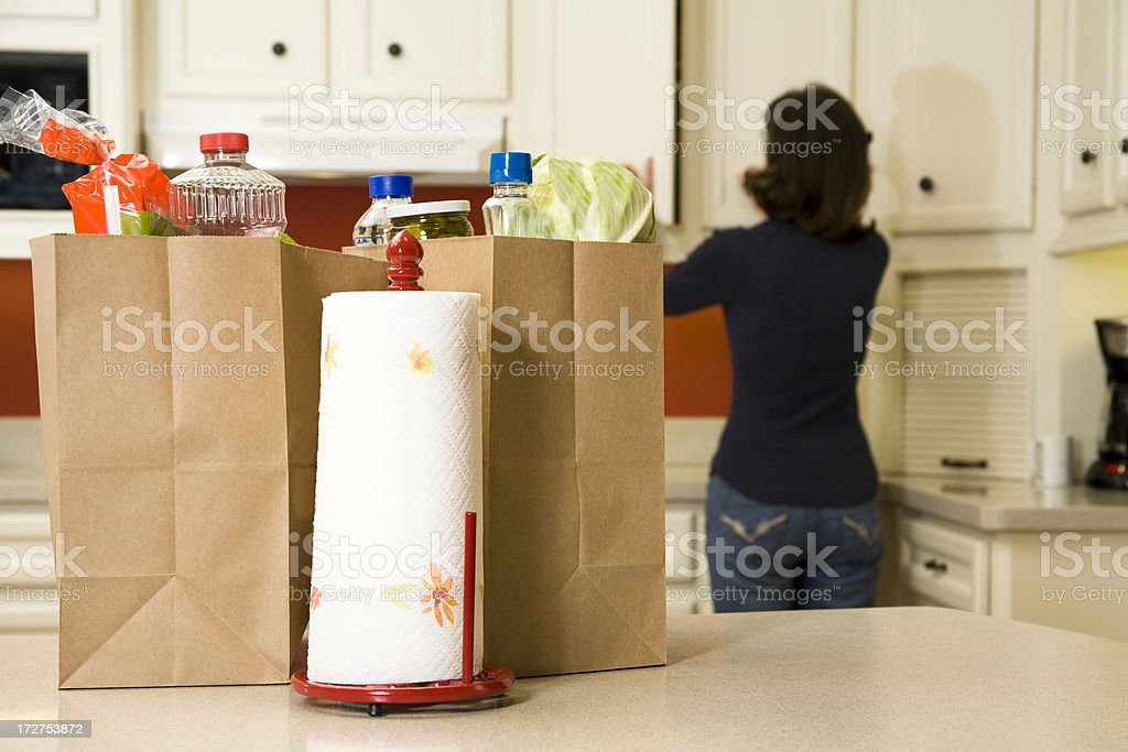 Food:  Bags of groceries on the home kitchen counter. Woman. royalty-free stock photo