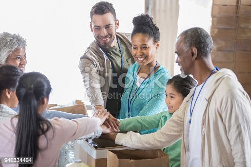 866758230 istock photo Food bank volunteers with hands together in unity 946334464