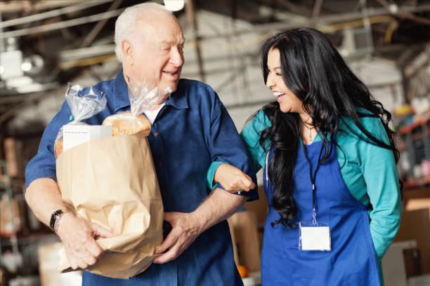 a food bank worker walks arm in arm with a senior patron - fondazione di beneficienza foto e immagini stock