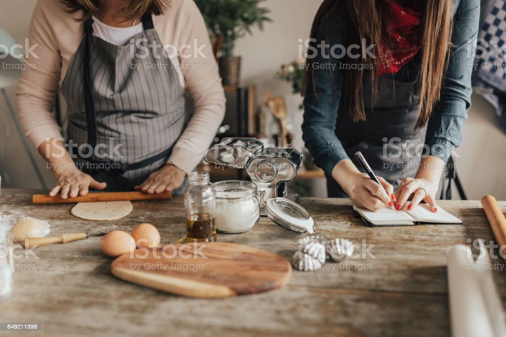 Food bloger writing down recipe in notebook. stock photo