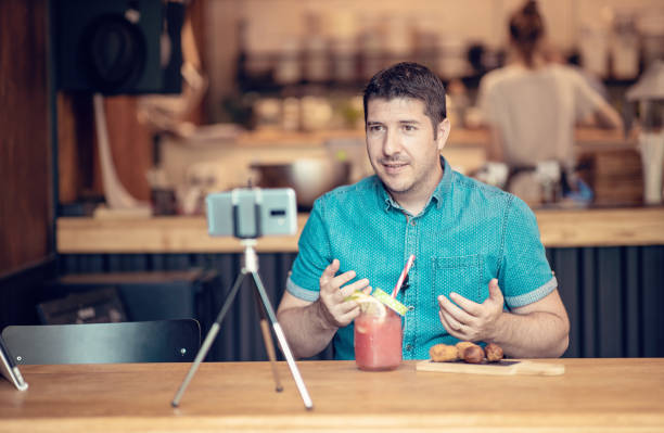 Food blogger man creating content in a small restaurant stock photo