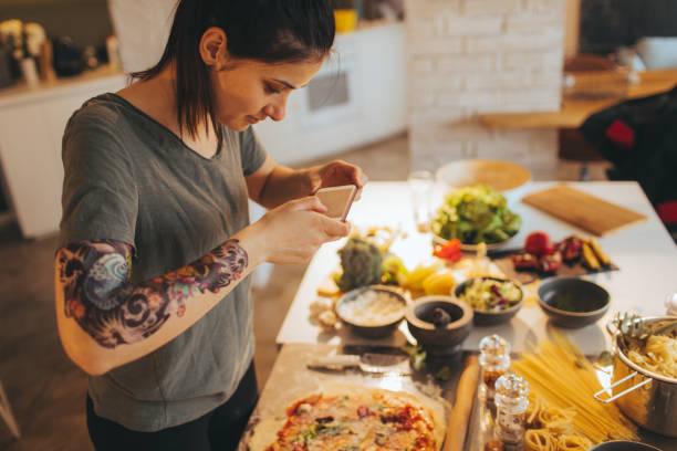 food-bloggerin fotografieren essen - essen tattoos stock-fotos und bilder