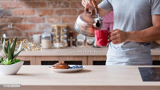 healthy food and quick breakfast. morning meal. poppy seed bun fresh and blueberry a kitchen table. man pouring boiling water from kettle to make tea in a red mug.