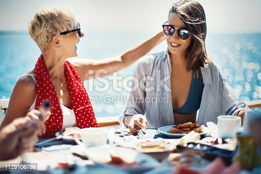 Mother and daughter enjoying family breakfast on the sailing boat.